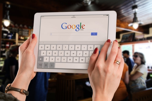 person holding a tablet opening google