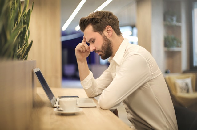 man frowning in front of computer