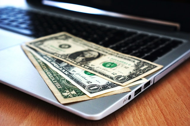 Money bills on top of a laptop