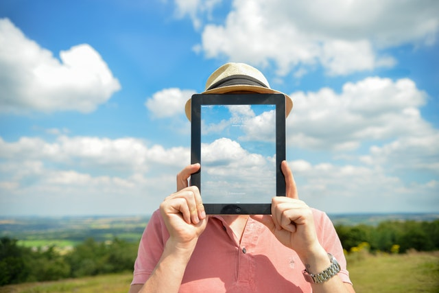 man holding an ipad showing clouds