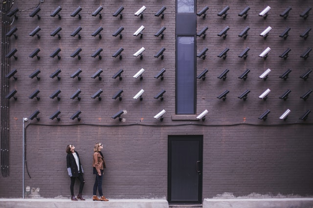 two people standing under dozens of CCTV