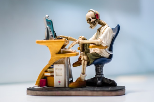 small statue of a skeleton using a computer