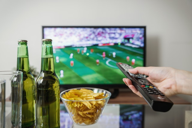 person watching a soccer match on TV