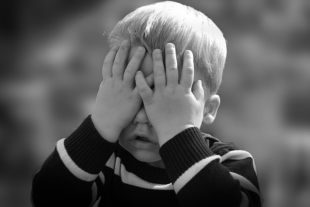 child hiding his face with his hands